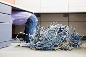 Computer Technician Crawling Under Desk