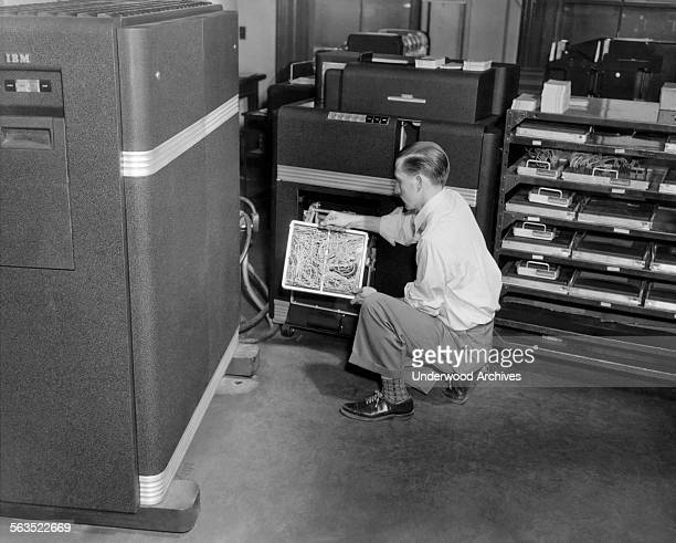 A computer technician holding a wired circuit board installed in an IBM punch card machine Cleveland Ohio circa 1952