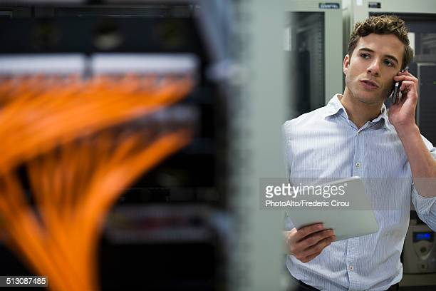 Computer technician performing maintenance check of mainframe equipment