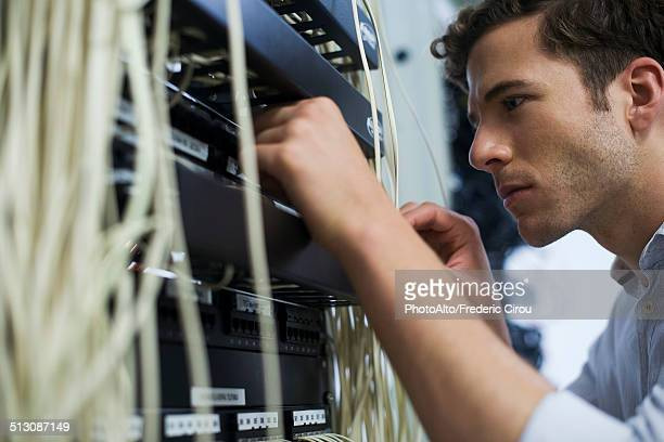 Computer technician performing maintenance on computer networking equipment