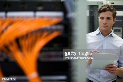 Computer technician using digital tablet performing maintenance check of mainframe equipment