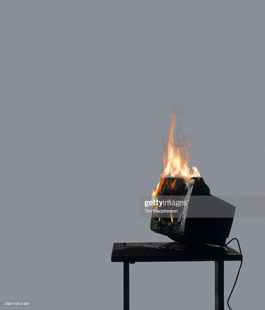 Computer terminal on fire on table (Digital Composite) : Stock Photo