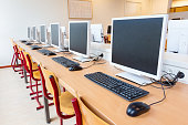 Computer education in classroom on high school. On this long table you see many desktop computers with keyboards and computer mouses. Also many chairs for the children to sit and work with the compute