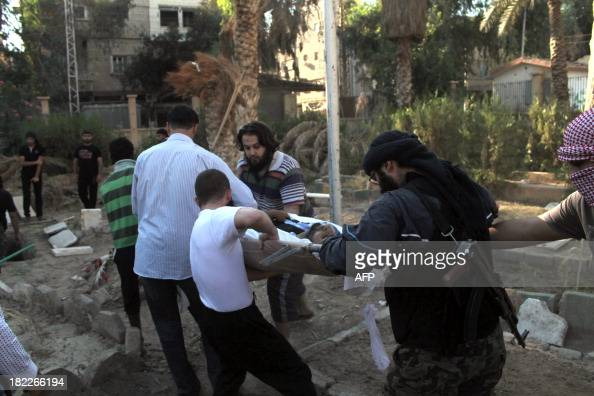 Comrades carry the body of a Syrian photojournalist and media activist Murhaf alModhi known as Abo Shuja towards his grave during his funeral in a...
