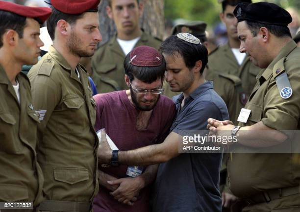 Comrades look on as relatives of Israeli soldier Sgt Yehuda Greenfeld mourn during his funeral at the military cemetery in Jerusalem 07 August 2006...