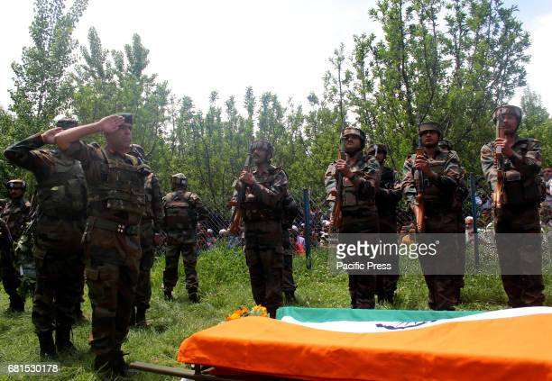 Comrades offer gun salute during the funeral procession of lieutenant rank army officer Umer Fayaz Parray resident of Sursunoo Yaripora area of...