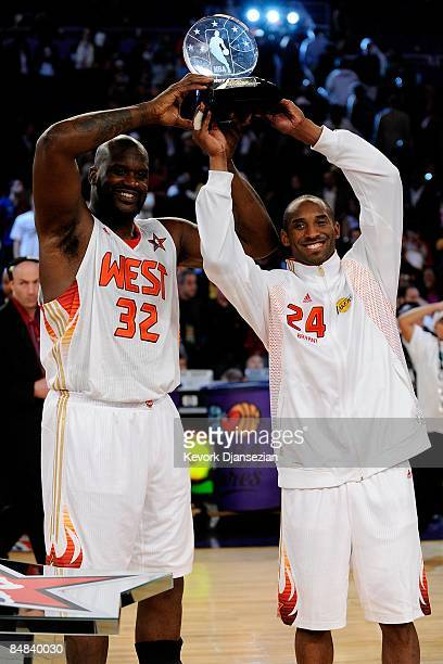 CoMVPs Shaquille O'Neal and Kobe Bryant of the Western Conference hold up the trophy after the Western Conference defeated the Eastern Conference in...