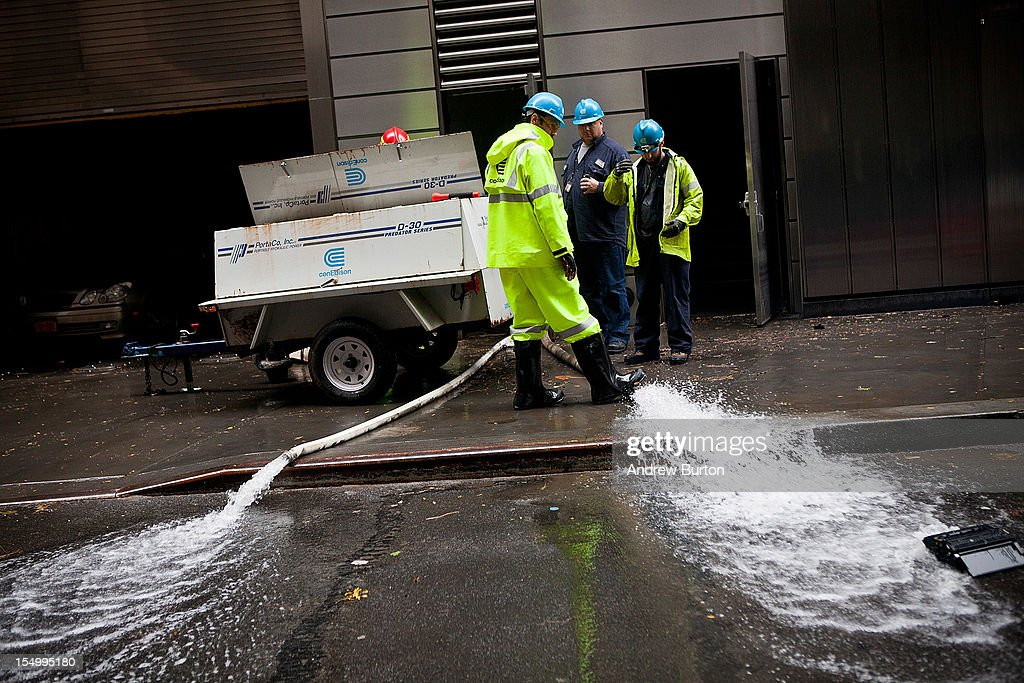Con Edison employees monitor the drainage of water being pumped out of Seven World Trade Center, caused by Hurricane Sandy, on October 30, 2012 in the Financial District of New York, United States. The storm has claimed at least 33 lives in the United States, and has caused massive flooding across much of the Atlantic seaboard.