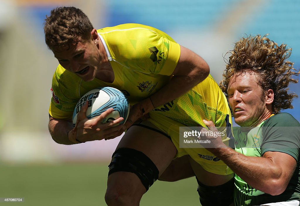 Con Foley of Australia is tackled by Werner Kok of South Africa during the 2014 Gold Coast Sevens Cup quarterfinal match between Australia and South...