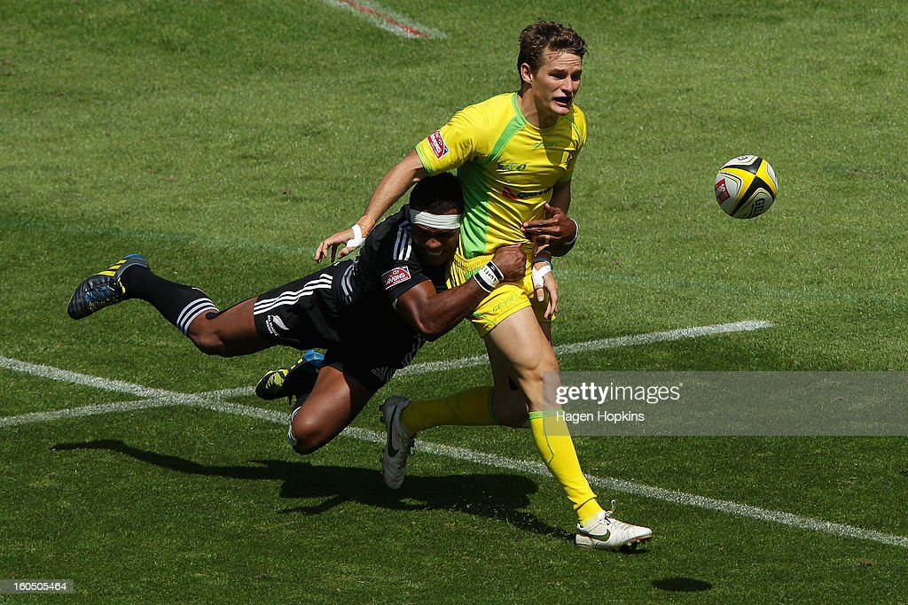 Con Foley of Australia passes in the tackle of Lote Raikabula of the All Blacks Sevens in the quarterfinal cup match between New Zealand and Australia during the 2013 Wellington Sevens at Westpac Stadium on February 2, 2013 in Wellington, New Zealand.
