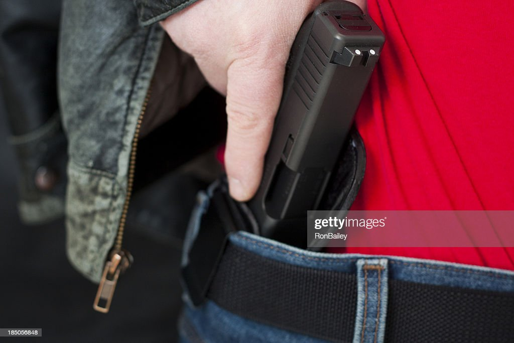 Concealed Carry Firearm Drawn From an Inside-the-Waistband Holster : Stock Photo