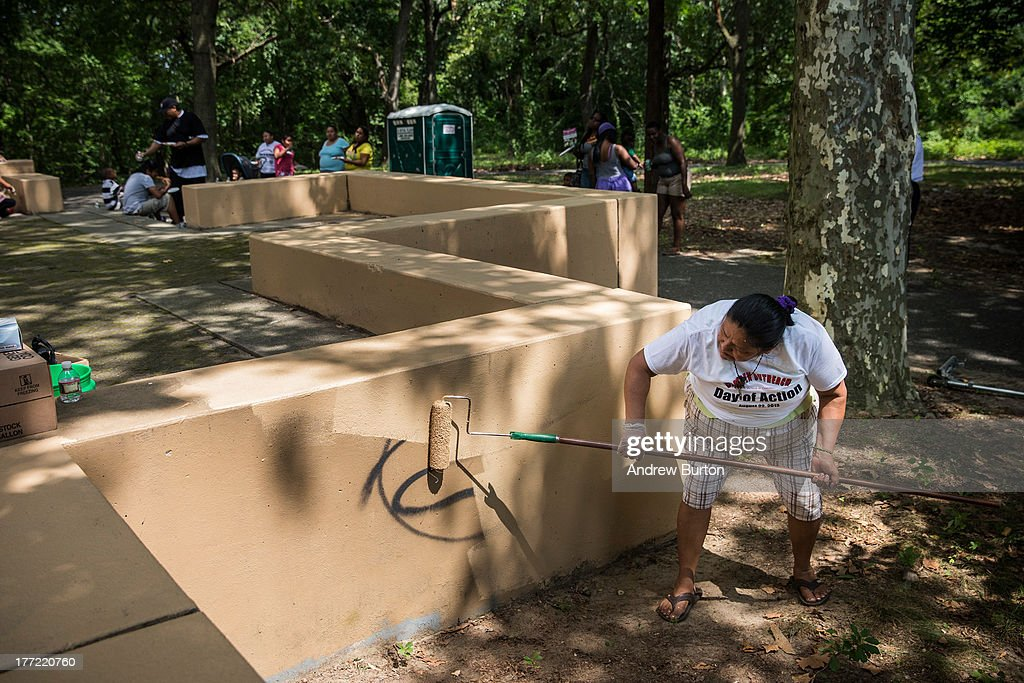 Concempcion Gutierrez, a volunteer, paints over a grafittied structure in Farnham Park, during a day of action, organized by Camden County Police Department (CCPD), on August 22, 2013 in the Parkside neighborhood of Camden, New Jersey. The town of Camden, which was once a large industrial town but watched it's population dwindle as manufacturing left, has been marred with societal problems including high unemployment, crime, murder and heavy drug trafficking for decades. The Camden County Police Department was officially created in May, 2013, after the unionized Camden Police department was disbanded. The overhaul, which was supported by New Jersey Governor Chris Christie, has been considered unprecendented and has been closely watched around the country. The new force currently has approximately 280 members, and will reach full size by December, with 400 members. Early signs suggest the overhaul has been effective - The Wall Street Journal reported earlier this month that Camden murder rates fell 29% from May, 2013 to July 2013, compared to the same period last year. Absentee rates of the CCPD is also lower: approximately 5% of officers have been reported absent so far, compared to approxmiately 30% of the Camden Police Department prior to the change in command.