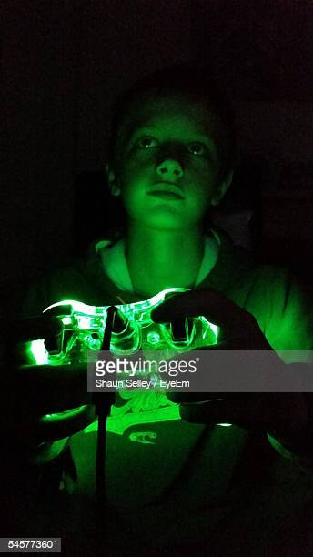 Concentrated Boy Playing With Green Illuminated Video Game