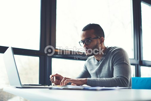 Concentrated businessman checking accounting documentation in online database on modern computer connecting to wireless internet connection. Male aro american entrepreneur working on laptop indoors : Stock Photo