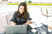 Concentrated mid adult businesswoman using laptop at table in garden