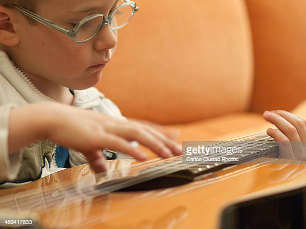 Concentrated child playing guitar