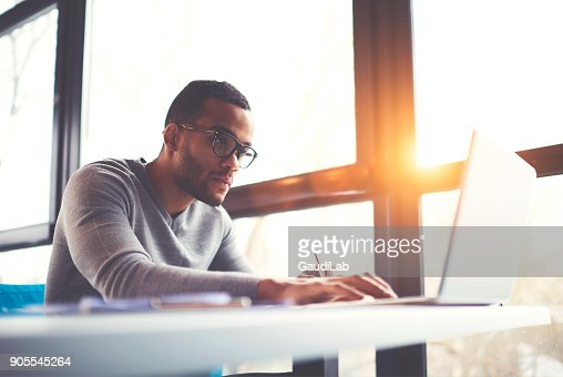 Concentrated dark skinned copywriter in eyewear typing text of publication for web site working on freelance, serious afro american student searching information for homework project in network : Stock Photo