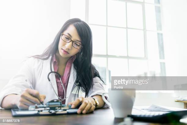 Concentrated doctor working at desk in clinic