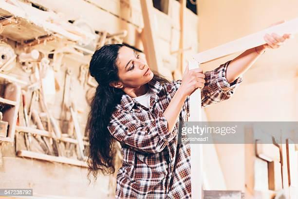 Concentrated female carpenter expertising a plank frame at workshop