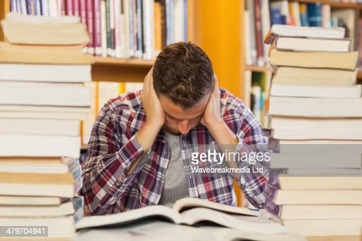 Concentrated handsome student studying between piles of books : Stock Photo