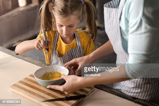 Concentrated little girl mixing eggs in the bowl : Stock Photo