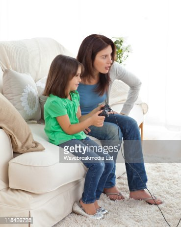 Concentrated mom and daughter playing video games : Stock Photo
