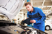 Concentrated young man in uniform examining car and writing something in clipboard while standing in workshop