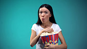 Concentrated woman chewing popcorn and watching exciting film in cinema, concept