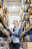Concentrated woman working with tablet in distribution warehouse