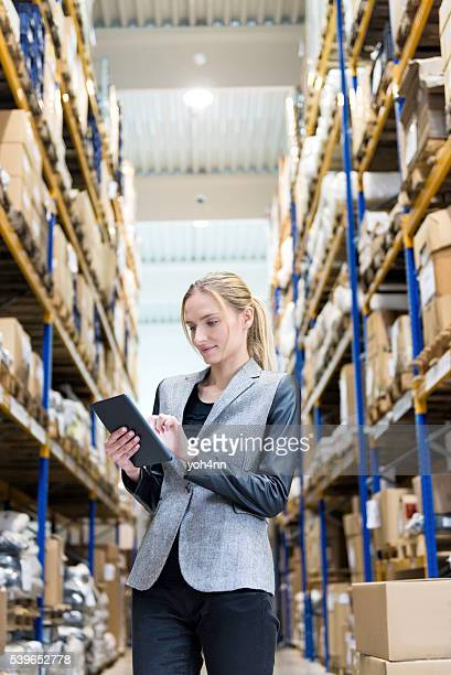 Concentrado mujer trabajando con tableta en almacén de distribución