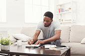 Concentrated young black man preparing for exams at home on couch, copy space