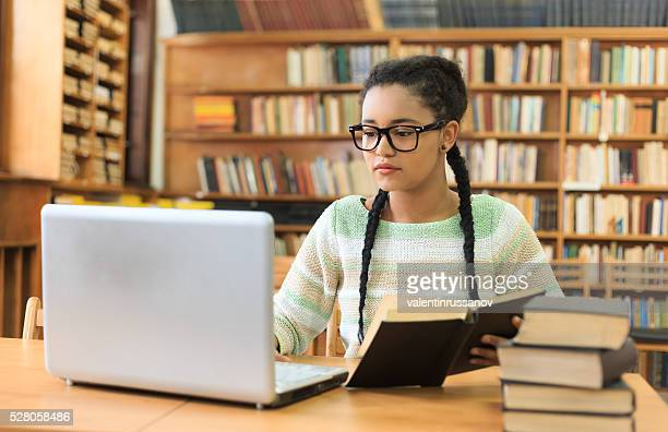 Concentrated young woman using a laptop in the library