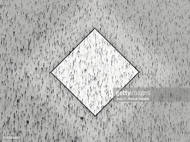 Concentric geometric forms of gray on a brown background with water droplets