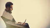 Concept, depicting business trip. Image created using multiple exposures. Portrait of a bearded businessman with a laptop and a long road. There is space for your text.
