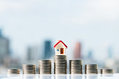 Red house model on top of coins stack with city backgrounds.