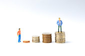 Concept for success ladder Miniature people: Small business figure standing on stack of coin. Money and financial concepts.
