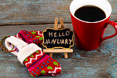 Concept HELLO january message on blackboard with a Cup of coffee and mittens.