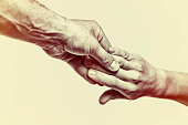 Male hand holds the female palm on toned, isolated,  background. That could mean help, guardianship, protection, love, care etc. This Image isolated for easy  transfer in your design.