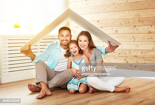 concept housing   young family. Mother father and child in new house with  roof : Stock Photo