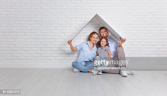 개념 주택 젊은 가족. 어머니 아버지와 자식 빈 벽돌 벽에 지붕 새 집 : 스톡 사진