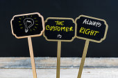 Concept message THE CUSTOMER IS ALWAYS RIGHT and light bulb as symbol for idea written with chalk on wooden mini blackboard labels, defocused chalkboard and wood table in background