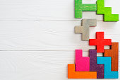 Concept of creative, logical thinking.  Different colorful shapes wooden blocks on white wooden background, flat lay, copy space. Geometric shapes in different colors, top view. Abstract Background.