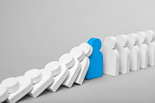 Concept of domino effect in business. The fall of the crumbling business is saved by special employee leader. The line of dominoes from the white figures of the man is falling, one blue man stops the