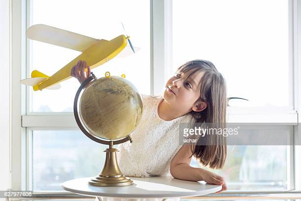 Concept of dreams and travels. Little girl and world