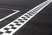 Checkered finish line on asphalt motorsport racing track concept of goal, achievement, success