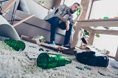 Concept of having headache after global party. Close up low-angle photo of empty green transparent beer bottles lying on nappy beige carpet, guy with nausea sitting on sofa in ob blurred background