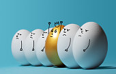 Concept of individuality, exclusivity, better choice and winning. A smiling golden egg with a crown among angry and sad white eggs on blue background. Eggs with funny drawn faces.