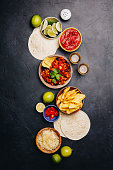 Concept of Mexican food (corn tortillas, nachos, salsa, avocado, limes, cheese, chili con carne) flat lay