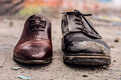 Conceptual shooting of shoes. Old shabby shoes in comparison with new and expensive ones.