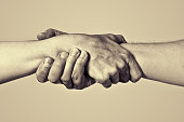 Concept of salvation. Image of the hands of two people at the time of rescue (help). Black and white.